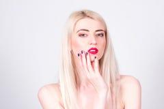 Mulher loura com bordos vermelhos e com um tratamento de mãos que toca em sua cara manicure Fotos de Stock Royalty Free