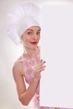 A mulher loura com cabelo curto em um chapéu e em um cozinheiro com o sorriso bonito que guarda um quadro de avisos branco Fotos de Stock