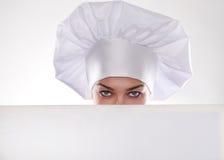 A mulher loura com cabelo curto em um chapéu e em um cozinheiro com o sorriso bonito que guarda um quadro de avisos branco Foto de Stock Royalty Free