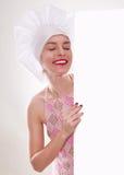 A mulher loura com cabelo curto em um chapéu e em um cozinheiro com o sorriso bonito que guarda um quadro de avisos branco Fotos de Stock Royalty Free
