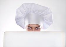 A mulher loura com cabelo curto em um chapéu e em um cozinheiro com o sorriso bonito que guarda um quadro de avisos branco Imagens de Stock