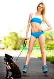 Mulher loura com o cão em patins de rolo no parque fotografia de stock