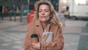 Mulher loura com o café que tirita com frio na rua do outono filme