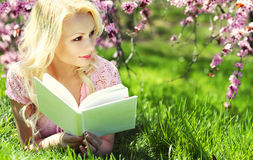 Mulher loura com o livro sob Cherry Blossom Imagens de Stock