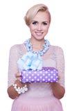 Mulher loura com o sorriso bonito que dá a caixa de presente colorida Natal feriado Foto de Stock