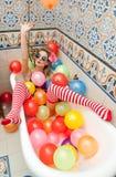 Mulher loura com os óculos de sol que jogam em seu tubo do banho com os balões coloridos brilhantes Menina sensual com as meias l Imagens de Stock Royalty Free