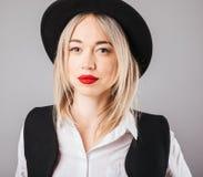 Mulher loura com os bordos vermelhos grandes no retrato do chapéu negro Fundo cinzento fotos de stock