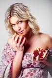 Mulher loura com a romã no cinza Fotos de Stock Royalty Free