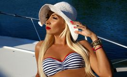 Mulher loura com um chapéu no roupa de banho no barco, verão imagem de stock