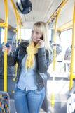 Mulher loura com um esperto-telefone dentro de um barramento Fotos de Stock Royalty Free