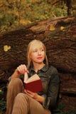 Mulher loura com um livro por uma árvore Fotografia de Stock Royalty Free