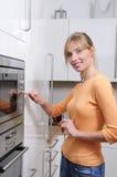 Mulher loura com uma microonda Fotos de Stock