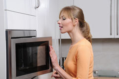 Mulher loura com uma microonda fotografia de stock royalty free