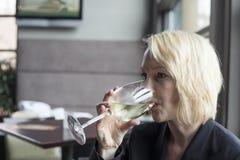 Mulher loura com vidro bebendo dos olhos azuis bonitos dos Wi brancos Foto de Stock Royalty Free