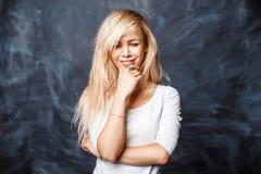 A mulher loura consideravelmente nova em um branco veste o sorriso em um b escuro Imagens de Stock Royalty Free
