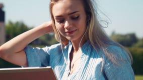 Mulher loura consideravelmente nova que escuta a música video estoque