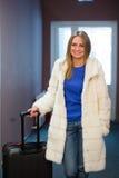Mulher loura consideravelmente nova que viaja vestindo um revestimento, calças de brim que puxam uma caixa do terno imagem de stock royalty free