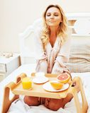 Mulher loura da beleza nova que come o café da manhã na ANSR ensolarada adiantada da cama Imagens de Stock Royalty Free