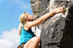 Mulher loura da escalada de rocha na corda ensolarada Fotografia de Stock Royalty Free