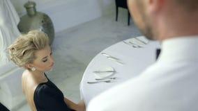 Mulher loura de fascínio que faz a ordem em um restaurante luxuoso filme