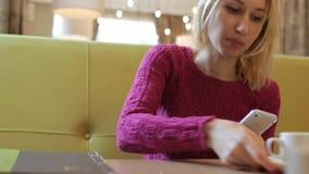 Mulher loura de sorriso feliz nova que usa o telefone celular no café bebendo do chá do café vídeos de arquivo