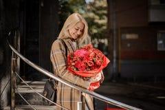 A mulher loura de sorriso na manta reveste com um ramalhete vermelho grande do flo fotografia de stock royalty free