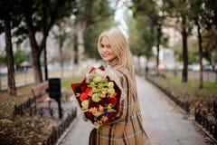 A mulher loura de sorriso na manta reveste guardar um ramalhete brilhante das flores que anda na aleia fotos de stock