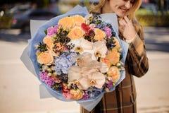 A mulher loura de sorriso na manta reveste guardar um ramalhete grande bonito das flores foto de stock royalty free