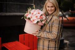 A mulher loura de sorriso no outono da manta reveste com uma caixa cor-de-rosa do flo imagens de stock royalty free