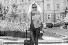 Mulher loura de sorriso nova com saco do curso e telefone que andam na rua da cidade, fêmea com os óculos de sol com o cabelo enc imagens de stock royalty free