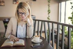 Mulher loura de sorriso nova em um restaurante que lê um livro e que bebe o café fotos de stock royalty free