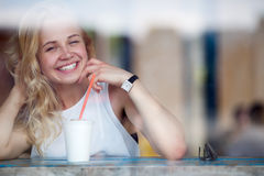 Mulher loura de sorriso que aprecia seu milk shake que senta-se no café imagens de stock