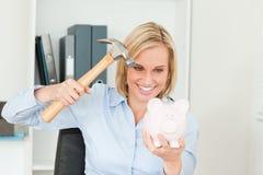Mulher loura de sorriso que destrói seu banco piggy Foto de Stock
