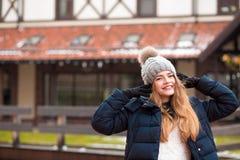 A mulher loura de sorriso que veste o inverno preto reveste e fez malha o chapéu p Fotos de Stock