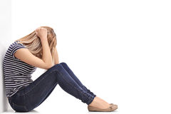 Mulher loura deprimida que senta-se no assoalho Imagens de Stock