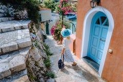 Mulher loura do turista do curso com chapéu do sol que anda através das ruas estreitas de uma cidade grega velha à praia férias fotos de stock
