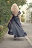 Mulher loura elegante bonita no vestido de seda longo maxi preto, partindo, fora, para trás Foto de Stock