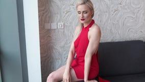 Mulher loura elegante ? moda na sala de visitas da casa, vestido 'sexy' vermelho vestindo video estoque