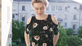Mulher loura em um vestido com as flores no fundo das ruas vídeos de arquivo