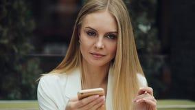 A mulher loura encantador lê algo em seu smartphone que senta-se na tabela no café vídeos de arquivo