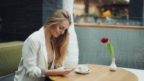 A mulher loura encantador lê algo em seu smartphone que senta-se na tabela no café video estoque