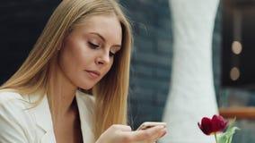 A mulher loura encantador lê algo em seu smartphone que senta-se na tabela no café filme