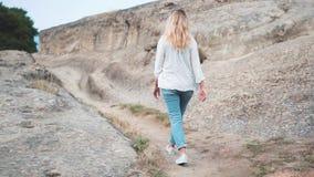 A mulher loura encaracolado nova nas calças de brim e em uma camisa branca anda no fundo da cidade antiga Turista em pitoresco filme