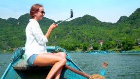 A mulher loura faz o selfie que navega no barco após o banco montanhoso vídeos de arquivo