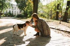 Mulher loura feliz com o cão no parque no dia ensolarado Imagens de Stock