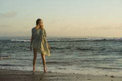 Mulher loura feliz e bonita nova que tem o divertimento na praia no vestido chique da forma que joga com o sentimento do mar aleg fotos de stock
