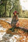 Mulher loura feliz no vestido cinzento da malha que senta-se no parque no aut Imagem de Stock