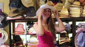 A mulher loura feliz nova escolhe o chapéu de palha na loja