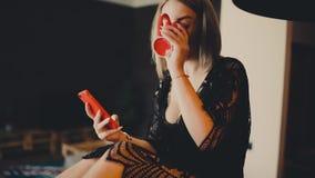 A mulher loura feliz nova que usa o smartphone comunica-se com o noivo que senta-se na tabela video estoque