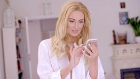 Mulher loura feliz que consulta em seu telefone celular filme